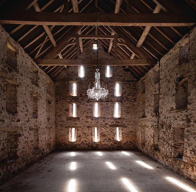 A gorgeous chandelier hanging from a timber truss sloped roof inside an old, empty stone building. Image by Fritz fryer.