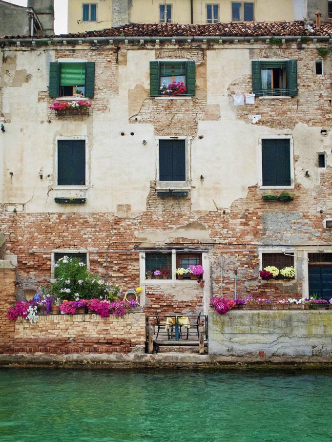 An old building in Venice with green Venetian blinds.