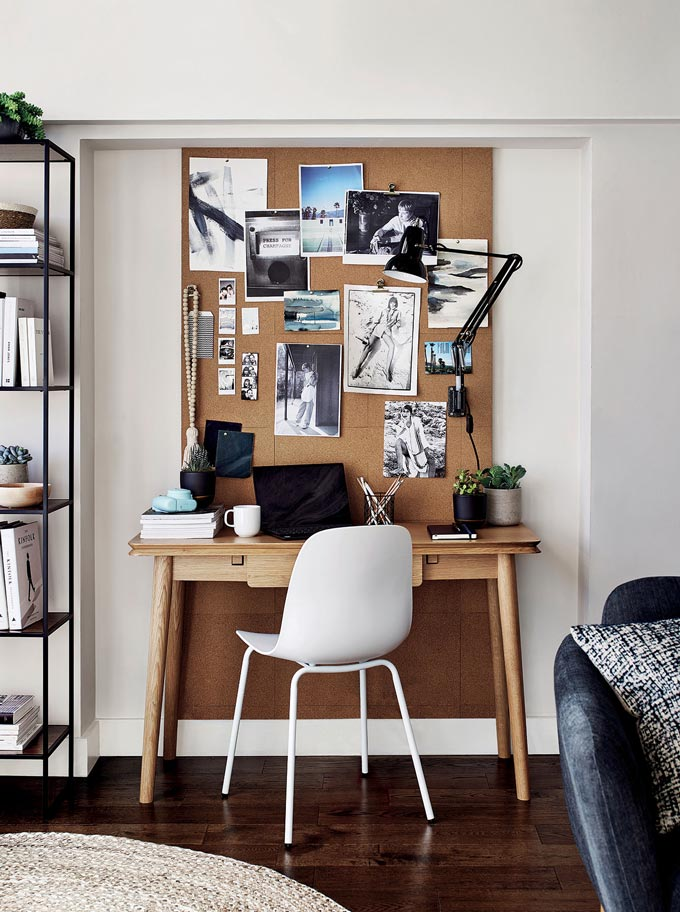 A home office vignette with a white desk chair, pinboard, wooden desk and black desk lamp. Image by John Lewis.