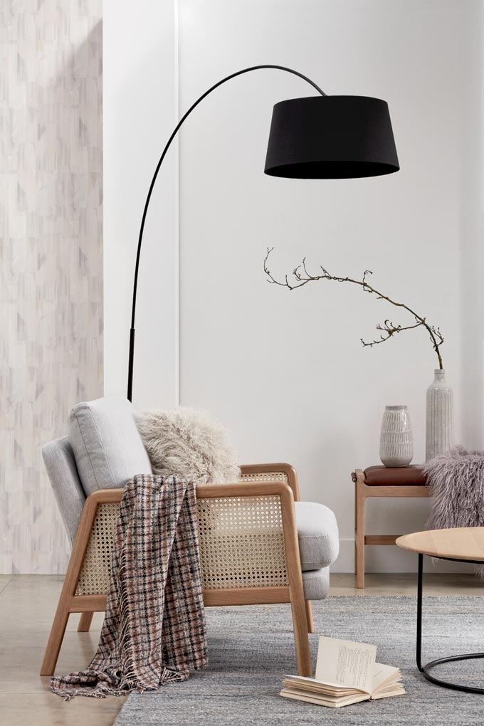 A floor lamp with a black shade adds definition in this vignette with a cane armchair and decorated side bench. Image by John Lewis.