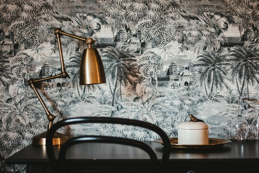 One of the six interior decorating fail proof tips calls for taking a risk - like adding wallpaper. A black desk and chair against a wall mural with a tropical theme and a copper desk lamp.