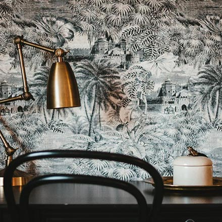 A black desk and chair against a wall mural with a tropical theme and a copper desk lamp.