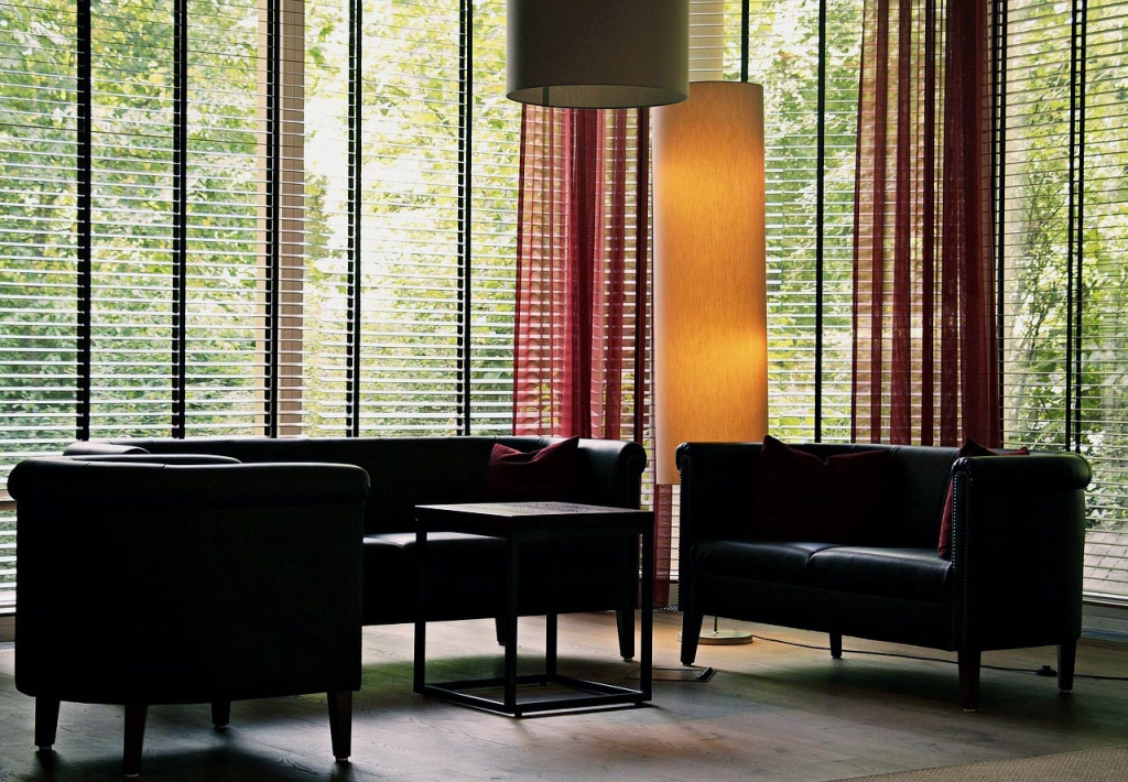 A lobby interior space with dark leather sofas and large bay windows from floor to ceiling with open Venetian blinds and view.