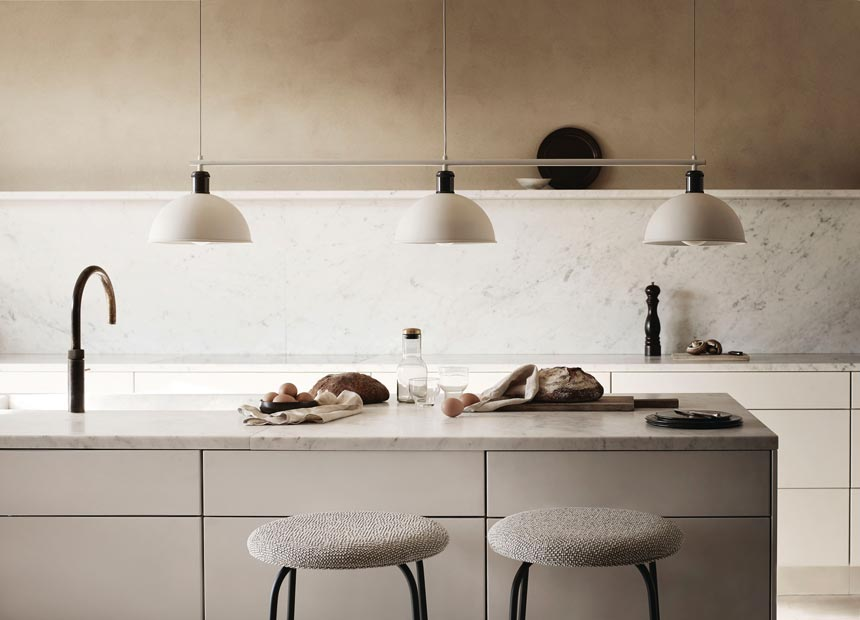 Three pendant lights hanging over a kitchen island. Image by Nest.