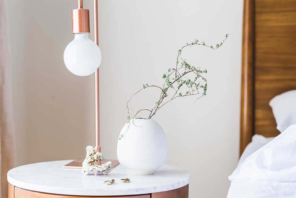 A copper table lamp on a nightstand next to a bed with a wooden headboard