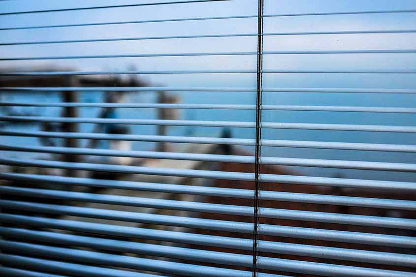 A close up detail of Venetian blinds as one looks outdoors through them