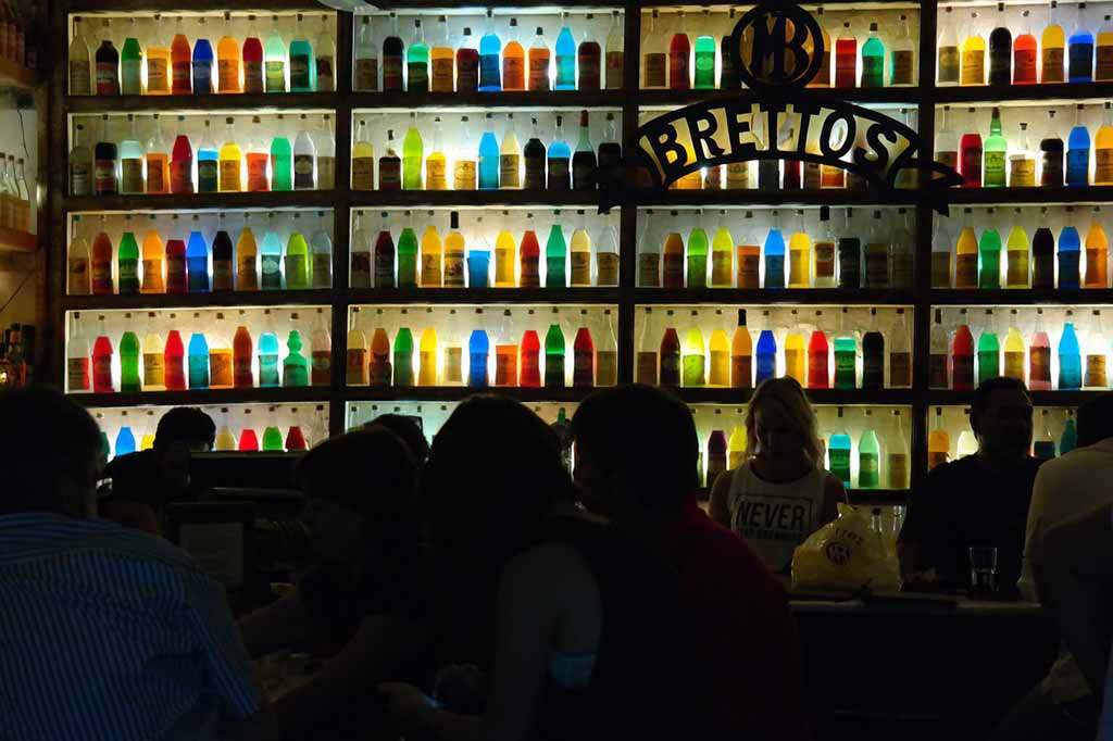 View of a pub's backdrop behind the bar made of shelving and colored glass bottles all lit up. One of the oldest bars in Athens