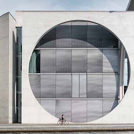 The exterior facade of a building with a tall concrete wall and a huge hole in it with large windows and Venetian blinds