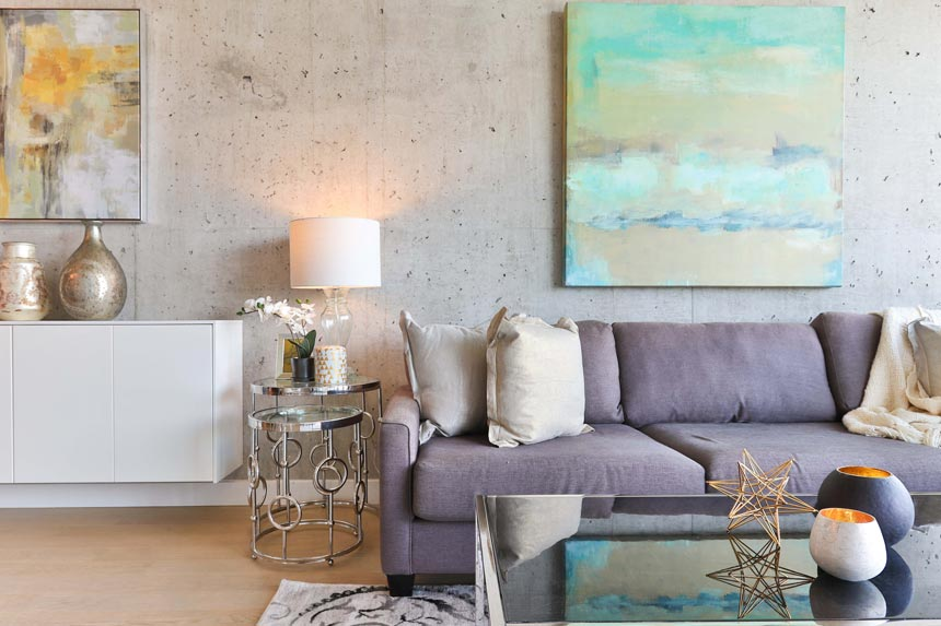 A stylish contemporary living room with beautiful artwork hangings and a large mirrored coffee table.