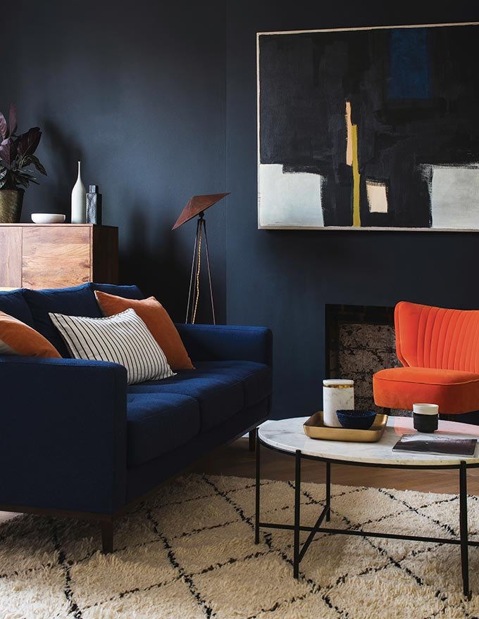 A dark blue living room with a dark blue sofa, an orange armchair, a round coffee table and an art image on the wall. Very eclectic and sophisticated indeed! Image by Swoon Editions.