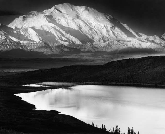 A classic landscape photo by Ansel Adams with mountains covered in snow in the background and a reflecting river meandering through.