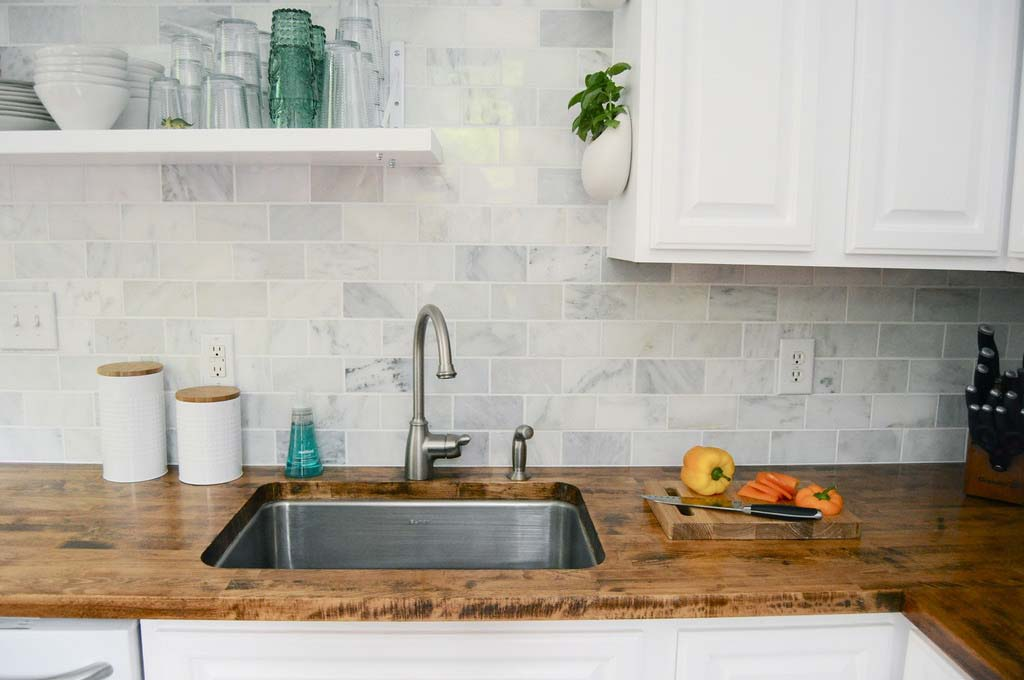 Detail of a wooden kitchen countertop with white marble tiles as backsplash and steel sink