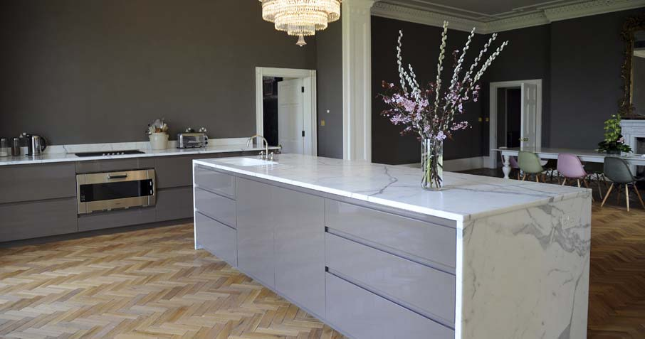 A contemporary minimal kitchen island with a marble top and sides in the middle of a room with hardwood flooring and a dining suite in the background