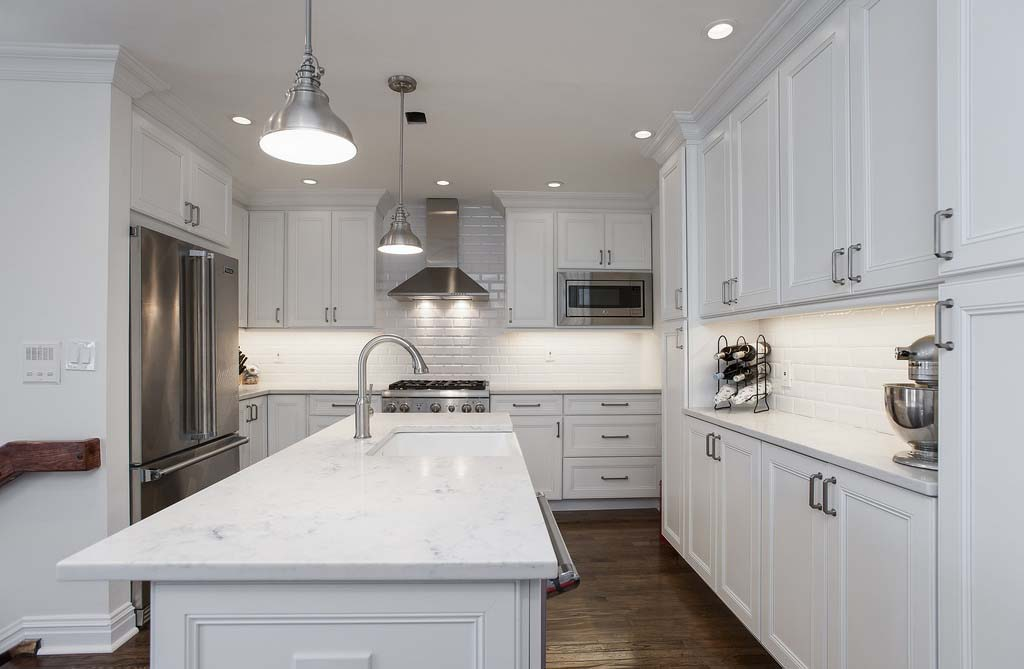 A white kitchen with white ceramic tile backsplash and white marble kitchen tops