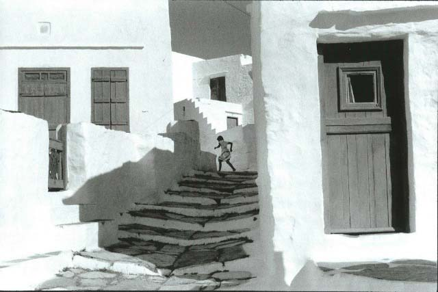 A classic black and white photo of old white washed houses aligned justify and right of a stone paved stairway, while a girl is running up.
