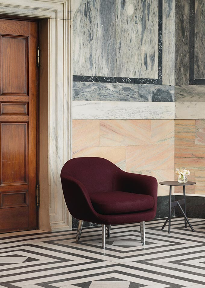 A comfy lounge chair in a prestigious looking space with marble flooring and wall cladding. Image by Nest.