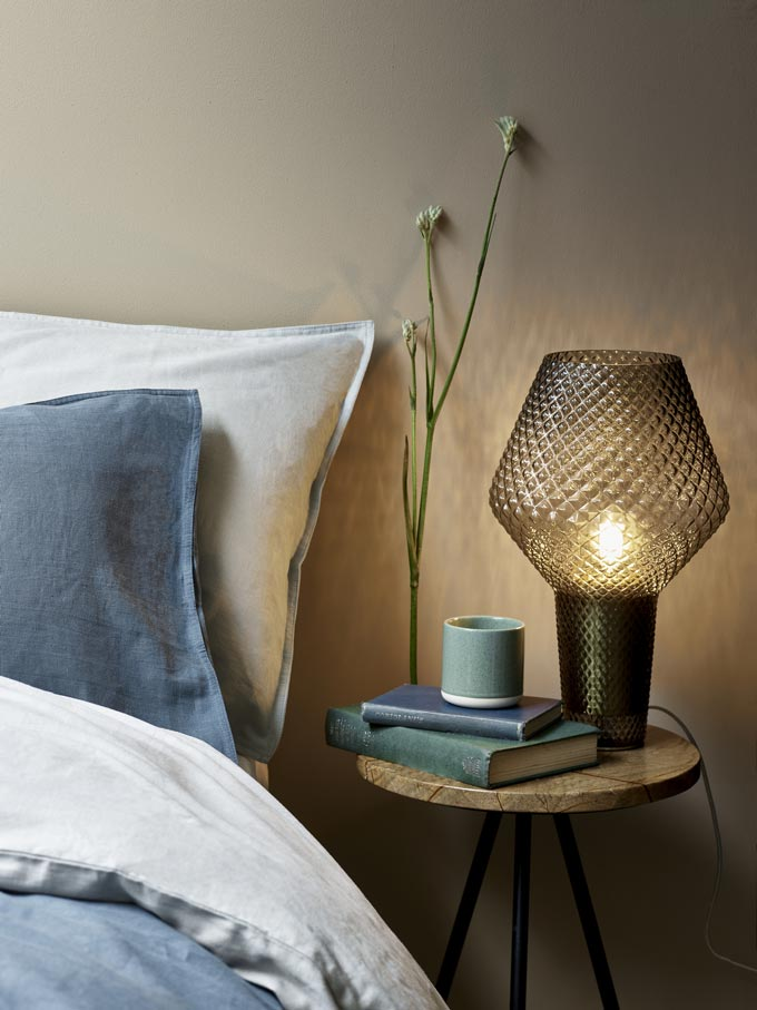 Close up of a bedroom vignette with a marble top side table as a nightstand by a bed. Image by Debenhams.
