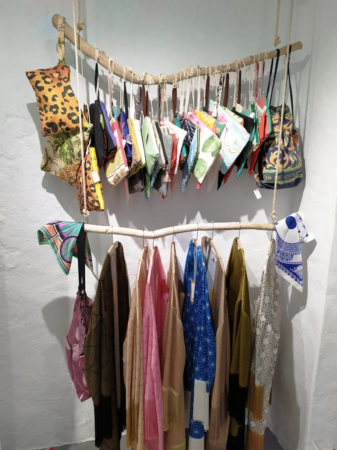 Accessories and boho inspired tunics on display at a Greek island retail store.