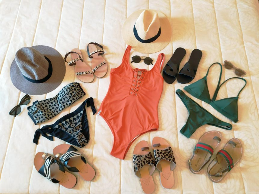 A flatlay with swimsuits, hats and flat sandals all suitable of packing to the Greek islands.