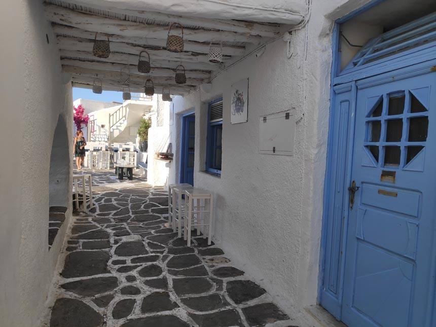 A underpass walkway with paved stone slabs near the scenic port of Naoussa in Paros.