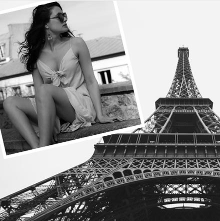 A black and white image of a young beautiful woman sitting somewhere outdoors wearing a summer dress. In the background image of the Eiffel Tower