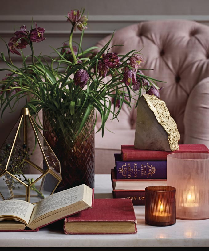 A close up of a white marble coffee table packed with tealights, books and a vase with flowers. In the background a blush pink armchair. Image by Marks & Spencer.