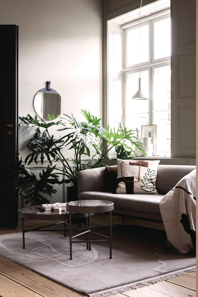 Ferm Living marble table in a contemporary muted beige living room with greenery and a large window. Image by Nest.