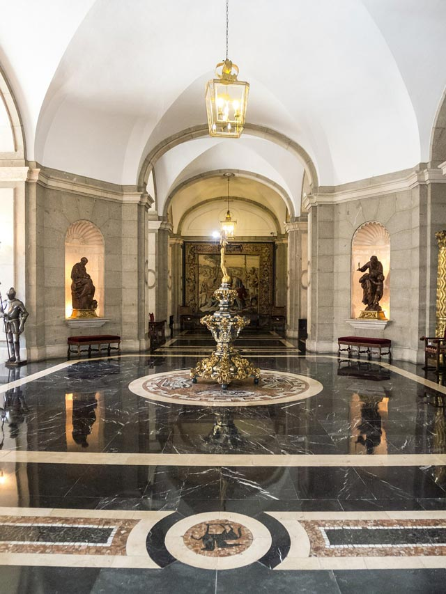 The interior of a palace room with black marble floors, high ceilings, and statues.