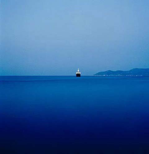 A ship in a deep blue sea under a clear blue sky. An amazing photo owned by Athens House Photography.