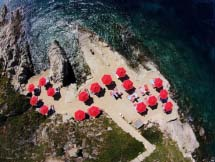 Photo print of a beach with red sun-umbrellas taken from atop. Image by Marina Vernicos.