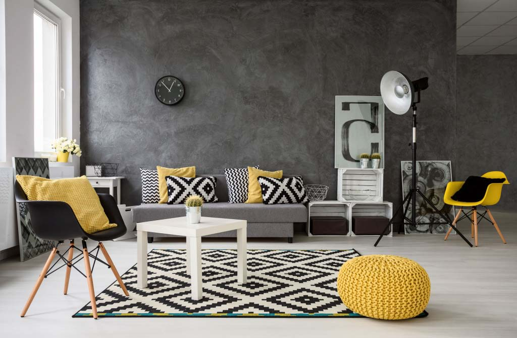 spacious, grey living room with sofa, chairs, standing lamp, small coffee-table, decorations in yellow, black and white. Behind the sofa there is a dark gray microcement accent wall