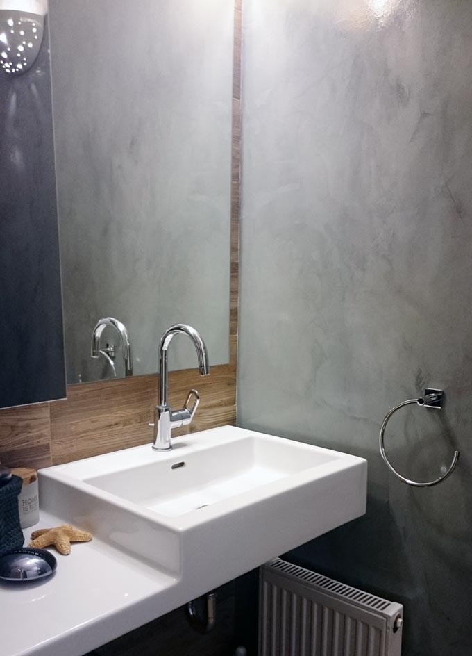 Partial view of my bathroom with its grey microcement wall and my white Laufen washbasin.