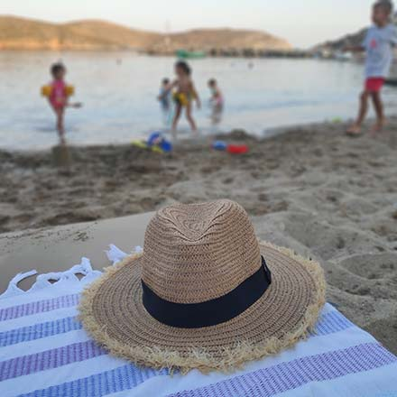 A straw hat on a beach towel by a sandy beach with children playing in the water in the background. Image by Velvet.