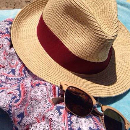 A straw Panama hat, a cover tunic with pink and blue patterns, sunglasses all resting on a turquoise beach towel
