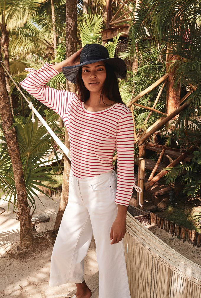 A young beautiful woman wearing a red Breton top, white wide leg jeans and a black hat. Very stylish indeed! Image by Long Tall Sally.