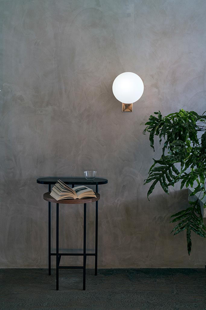 The &Tradition; Journey SHY2 wall light featured on a microcement wall. Image by Nest.co.uk.