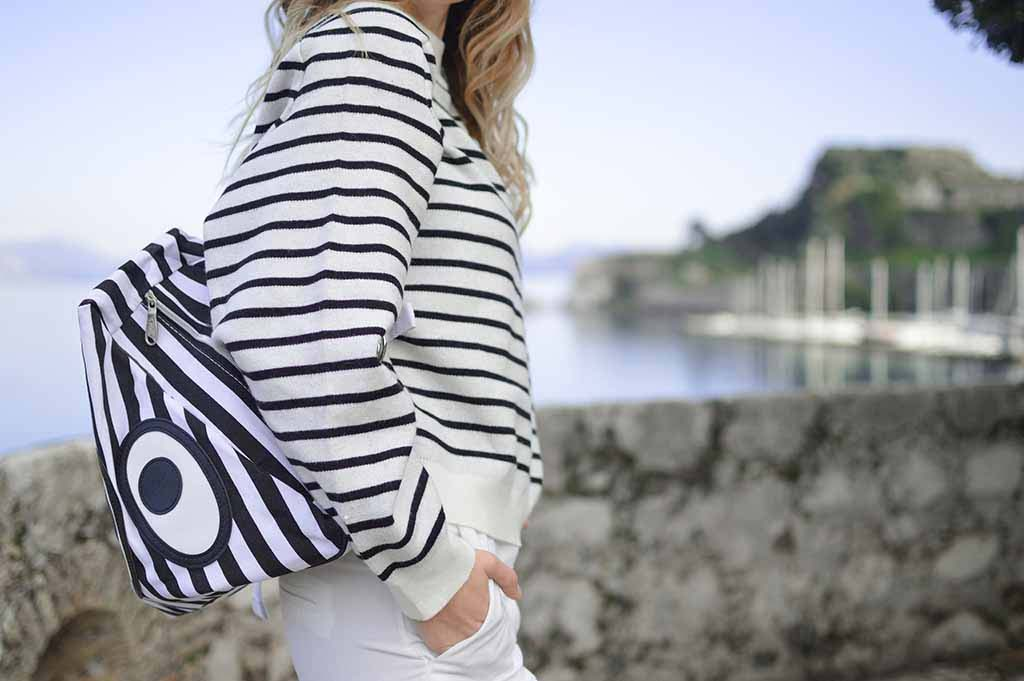 A blonde woman (whose face can't be seen) is wearing a Breton sweater and carrying a striped backpack somewhere by the seashore