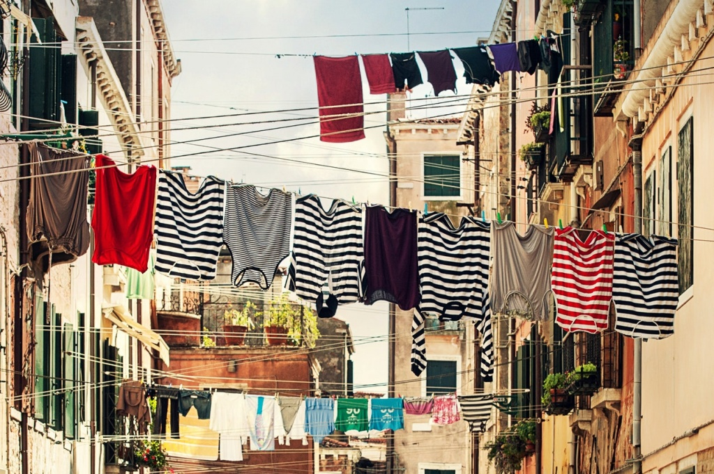 Several different Breton type tees hanging to air dry on a line between two buildings