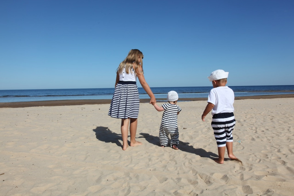 A little girl holding hands with a toddler baby and a little boy all dressed with Breton stripes are walking at a sandy beach