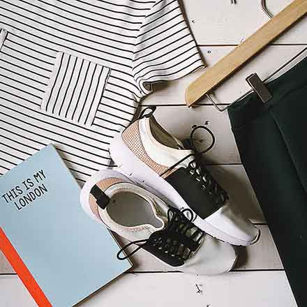 A flatlay of a Breton shirt, a notebook, a pair of shoes and a pair of black pants