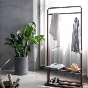 View of a room with a clothing rack in front of a window with white sheer curtain and a round tall concrete planter pot against a gray microcement wall