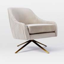 An off white swivel chair with a brass four legged stand