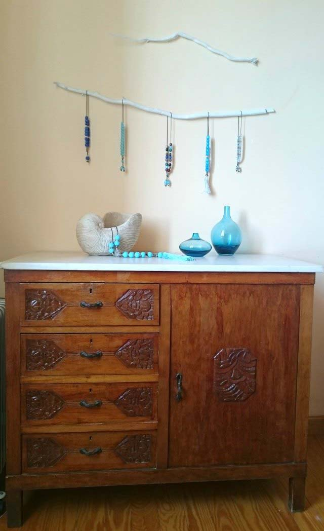 Two white tree branches hanging on the wall over an old wooden sideboard. The bottom branch has several worry beads hanging from it.