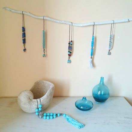 A white branch on the wall with worry beads hanging from it over a marble top with decor on it