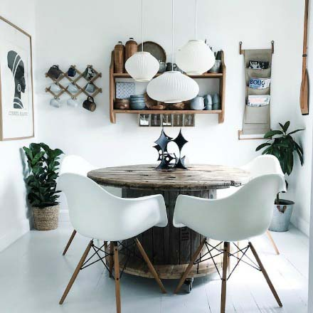 A white Scandinavian dining room filled vintage finds. There is a white three lamp pendant light hanging over a custom made rustic round table. There's also an open shelving unit on the wall with pots and mugs.
