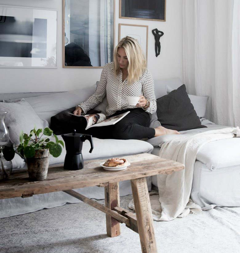 Slow design principles and Lagom: A blonde woman, Niki Brantmark, sitting on sectional gray sofa in the corner of her living room. There's a rustic coffee table and an art print gallery wall over the sofa and she's reading a book.