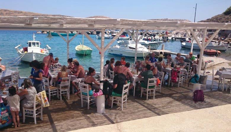 View of the Achladi taverna with many fishing boats docked nearby. Lots of people eating under a shade, while their feet are getting wet from the sea.