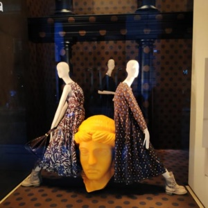 A window display from a women's store in Milan with three mannequins and a huge yellow bust. Image by Velvet.