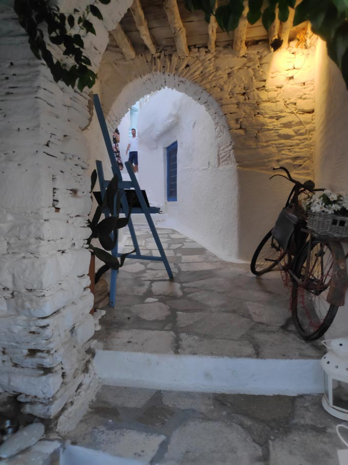 An old bike used as decor under an alley passage in Ano Syros. Image by Velvet.
