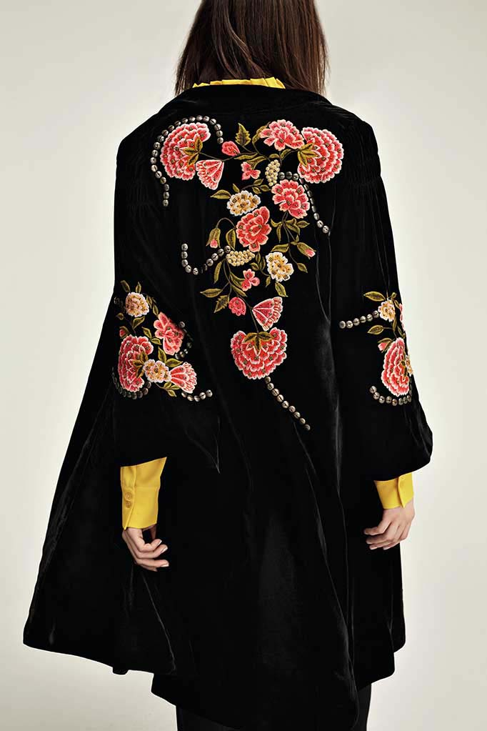 Red flower embroidery make this long black jacket stand out when worn over this yellow silk shirt. Image by House of Fraser.